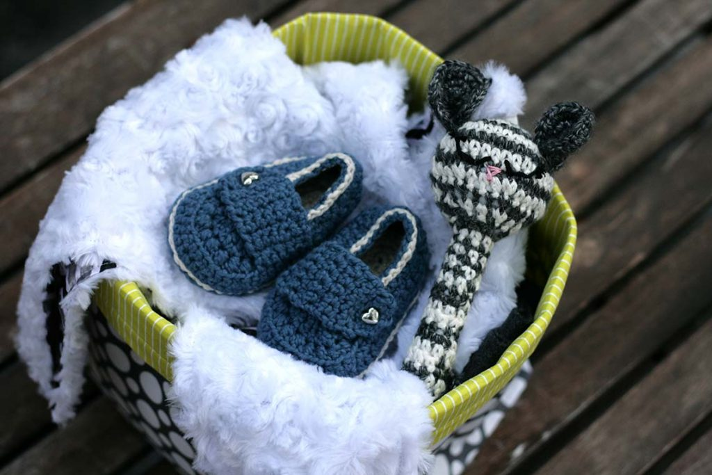Baby Buckets include Itty Bitty soft and silky baby blankets + spare bitty, crochet organic cotton baby bootie loafers and a crochet mouse baby rattle all contained in a fun and useful fabric basket.